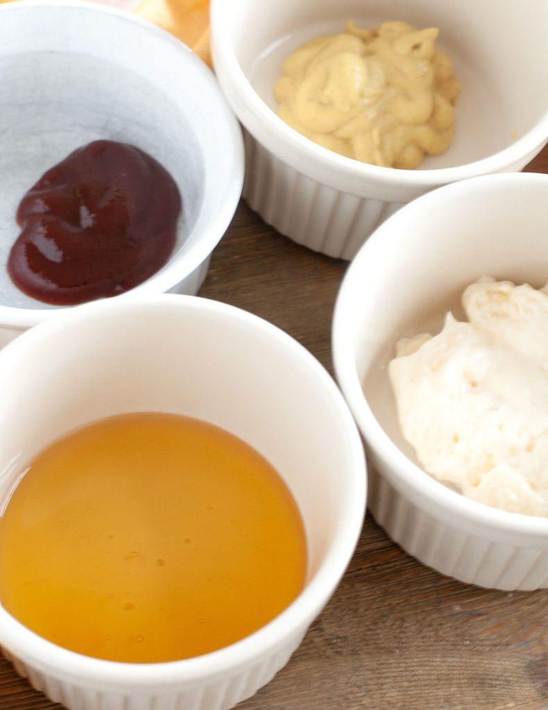 Bowls of BBQ sauce, honey, mayo and mustard