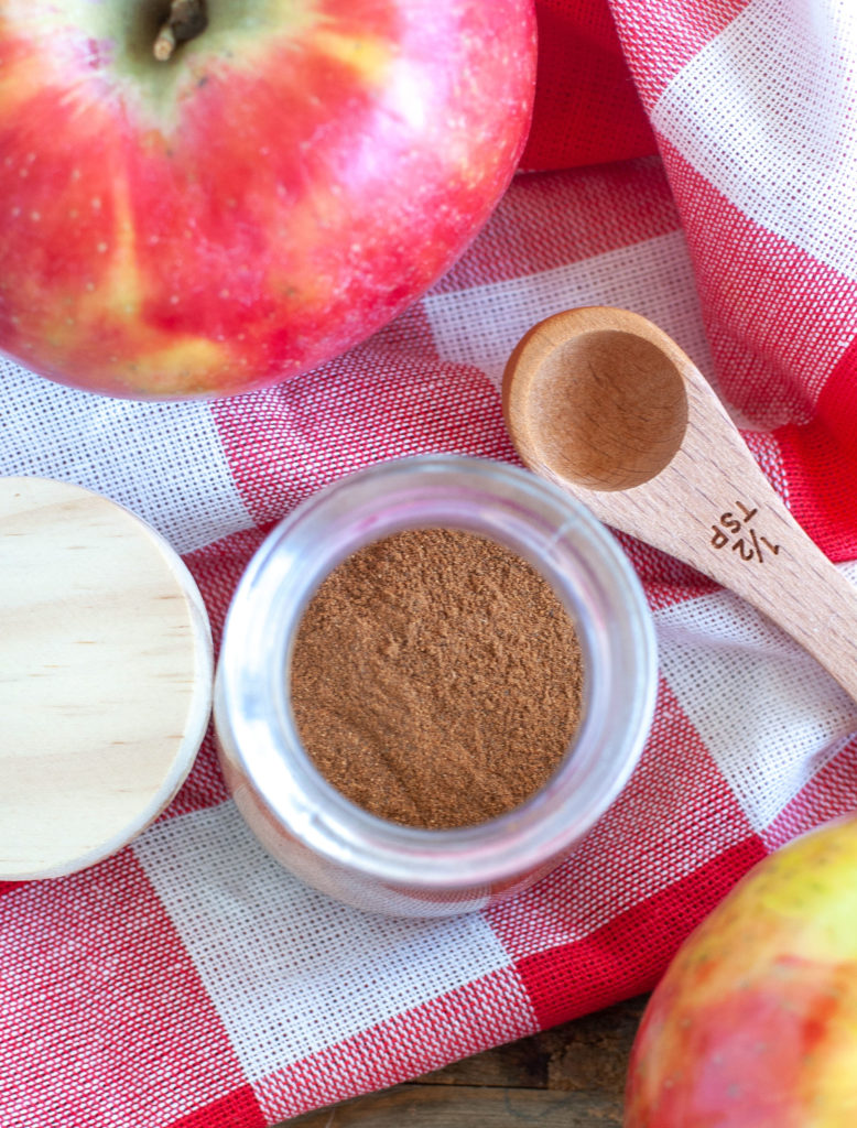 Apple Pie Spice in a jar and an apple and teaspoon