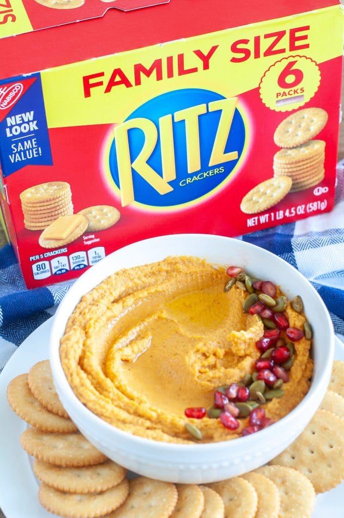 Bowl of pumpkin hummus with box crackers