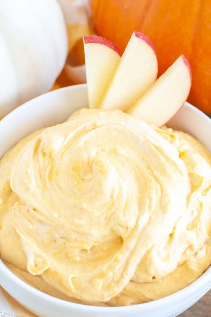 Bowl of pumpkin dip with 3 sliced apples