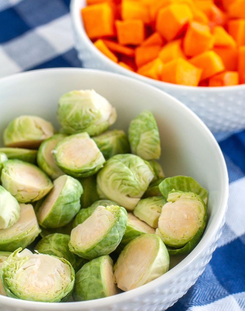Bowl of brussels sprouts and a bowl of cut up butternut squash