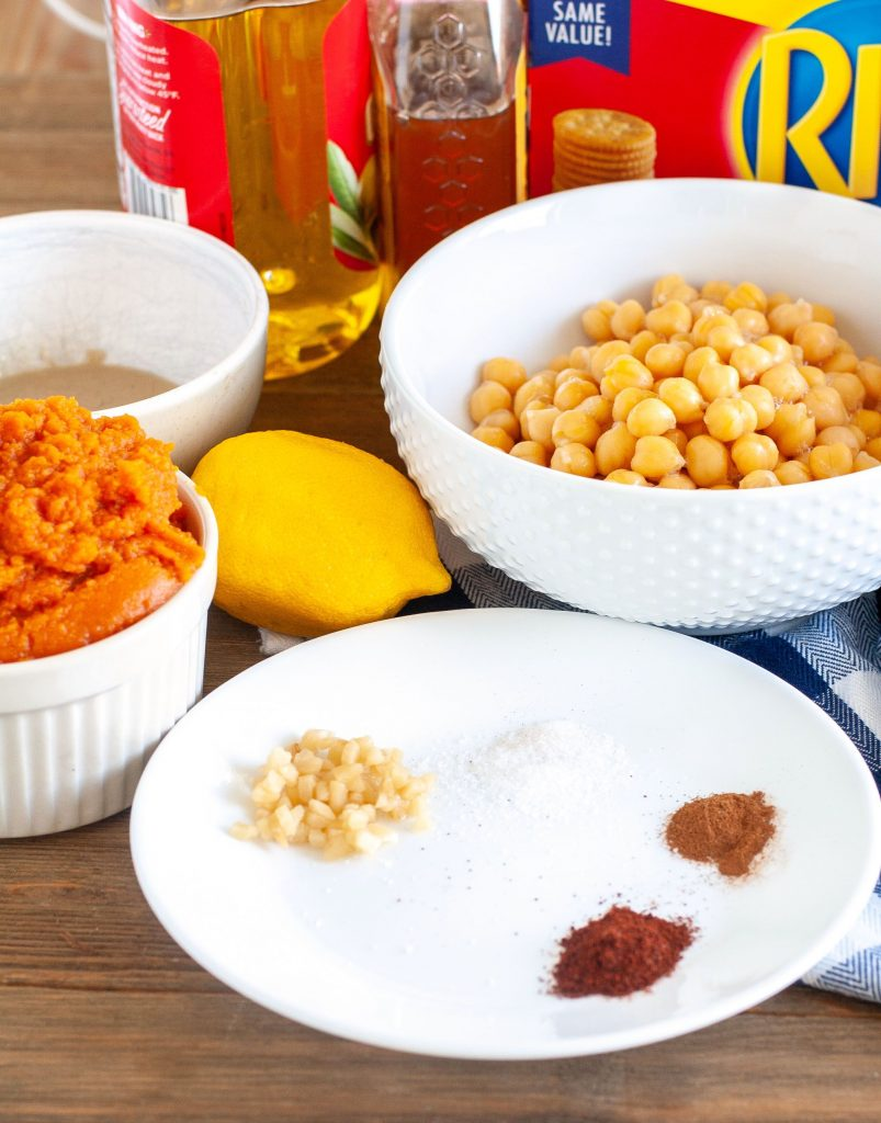 Bowl of pumpkin puree, chickpeas, spices, oil and honey