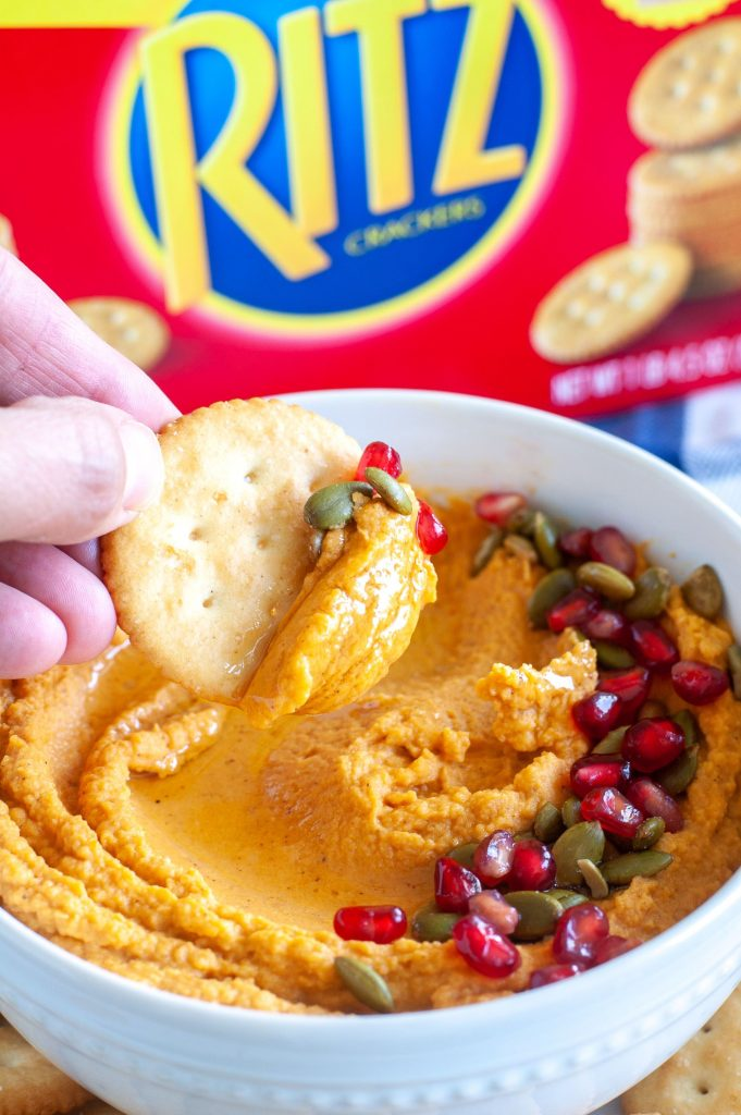 bowl of pumpkin hummus dip with a cracker dipping in