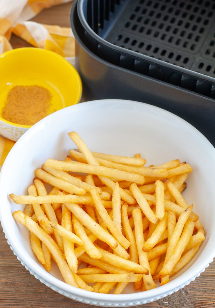 Bowl of air fried french fries with a bowl of season salt