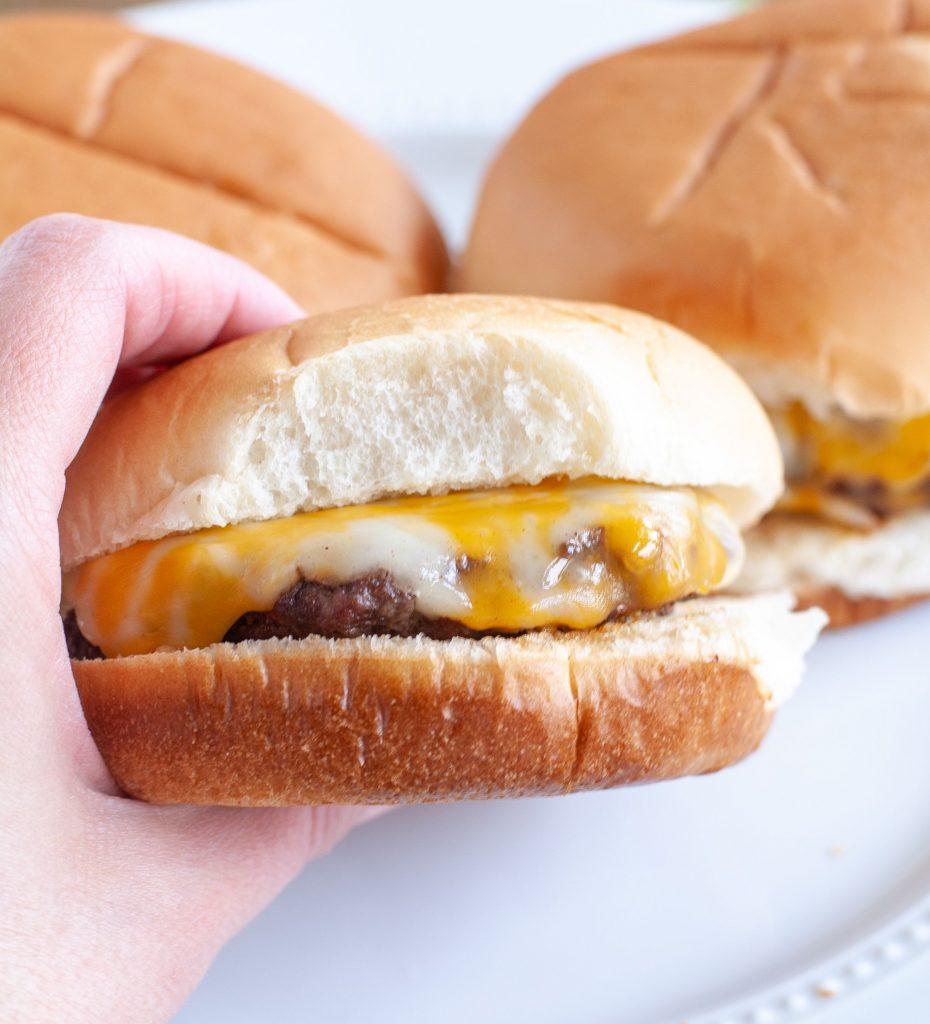Hand holding cheeseburger