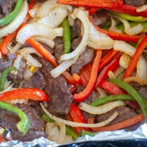 Steak, peppers and onions in foil.