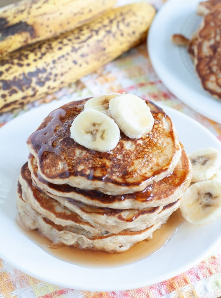 stack of pancakes topped with banana slices