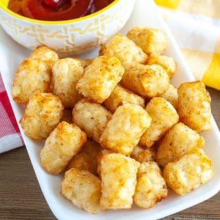 Tator Tots on a plate with bowl of ketchup