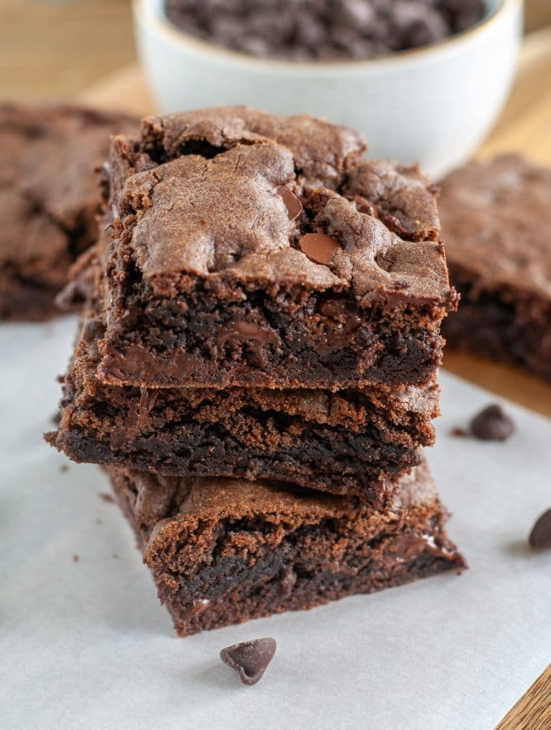 Stack of three brownies and chocolate chips.
