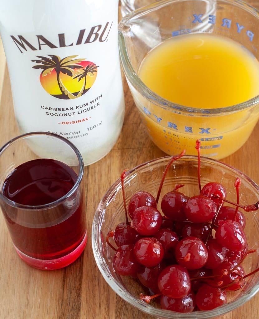 bottle of malibu rum, pineapple juice, bowl of cherries and cherry juice