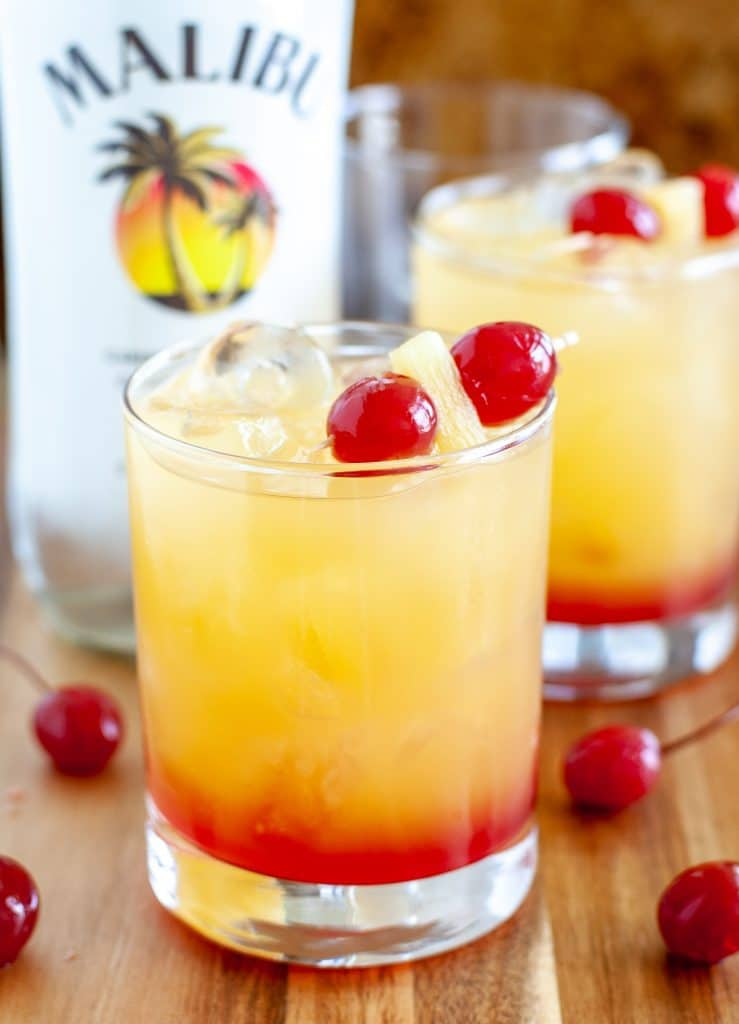 Rum cocktail in a glass with cherries and bottle in background
