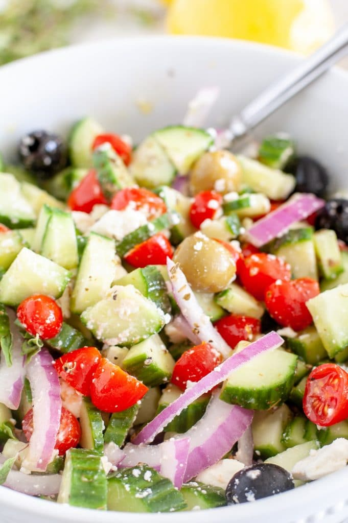 Cucumber tomato salad in a bowl with a fork