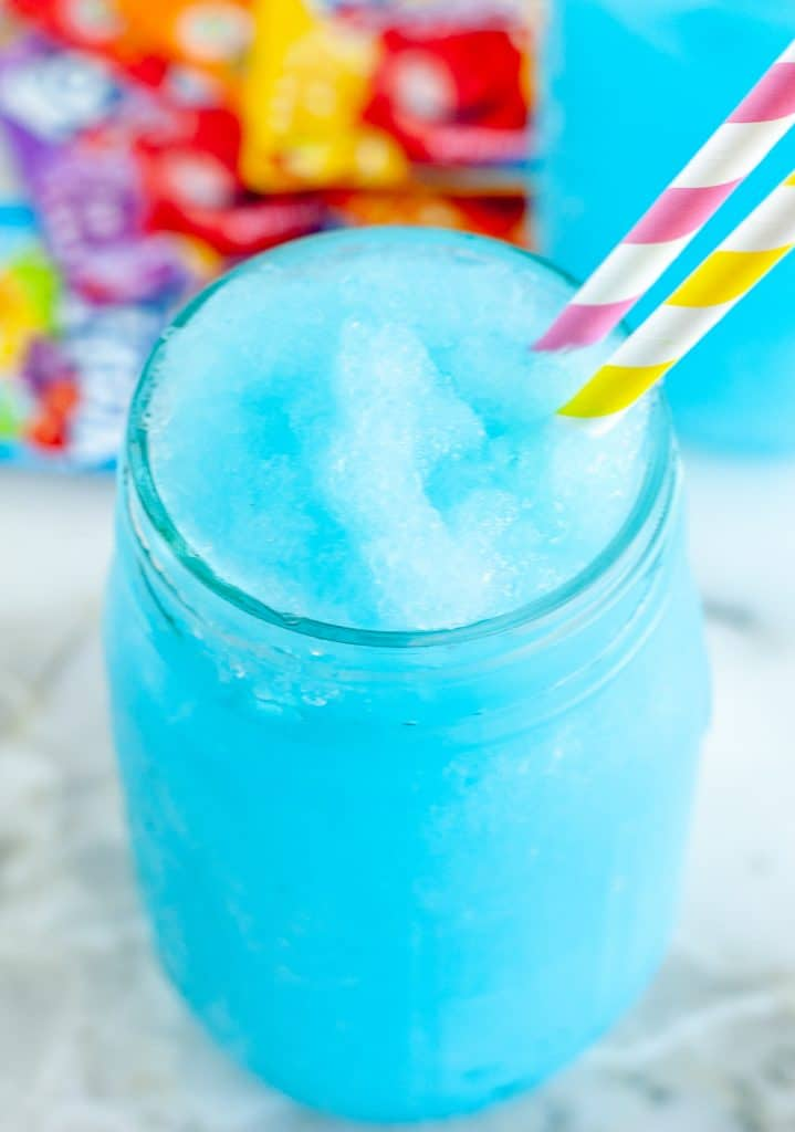 Blue slushie in a glass with kool-aid packets on the table