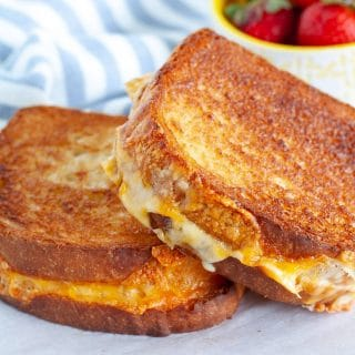Two grilled cheese sandwiches on a plate.