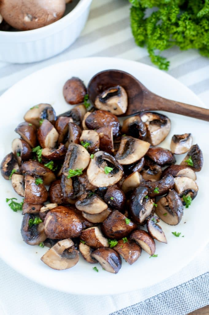 mushrooms on a white plate with wooden spoon