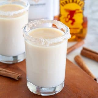 Cinnamon toast crunch shots with bottles in the back