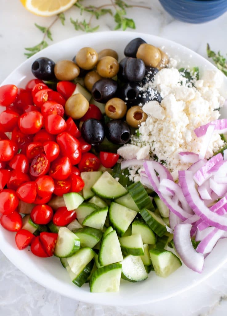 cucumbers, tomatoes, onion, olives and cheese in bowl