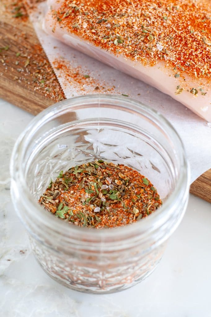 Spices in a jar with a piece of chicken and seasonings