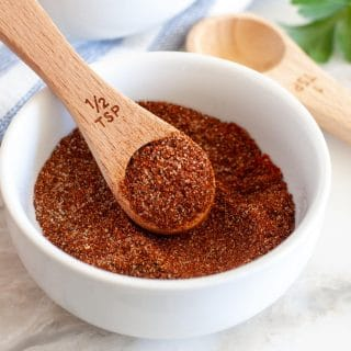 Chili spices in a bowl with wooden spoon