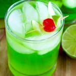 Glass with green drink and a cherry.