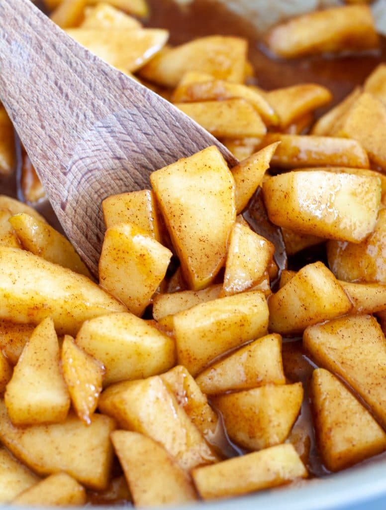 Skillet of cinnamon apples with wooden spoon