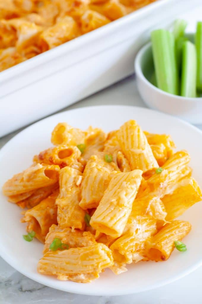 Buffalo chicken pasta bake on a plate with celery in a bowl