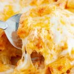 Spatula holding cheesy pasta casserole.