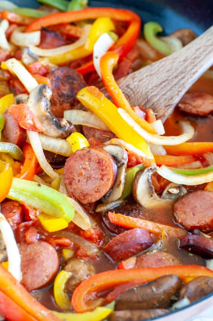 Wooden spoon with sausage and peppers.