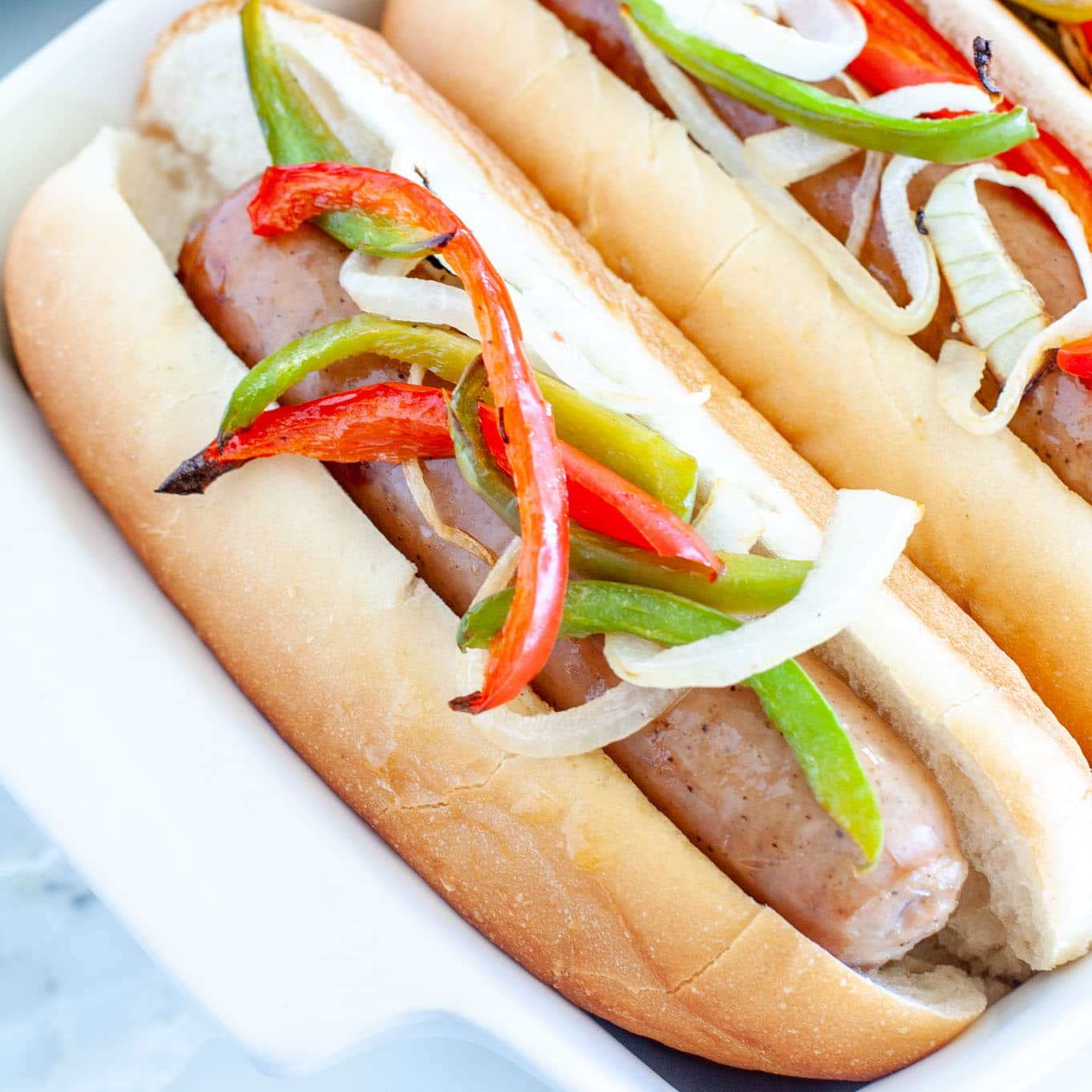 Brat in a bun with onions and peppers.