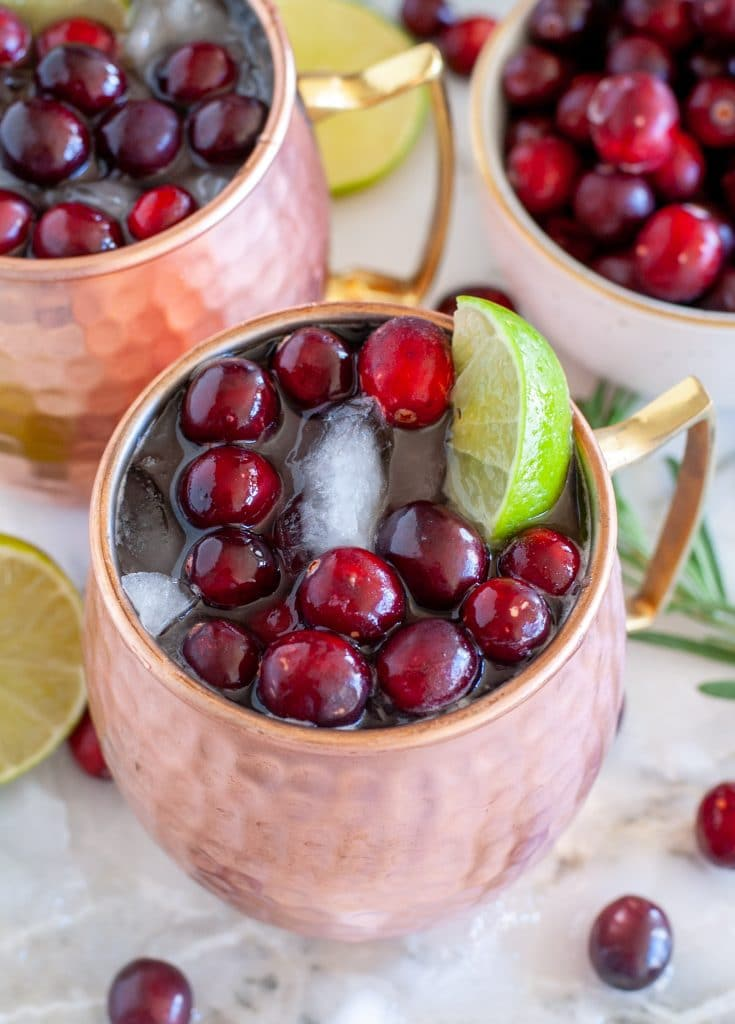 copper mug with cranberries, lime wedge and cranberry juice