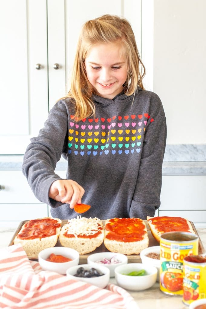 Girl making french bread pizza.