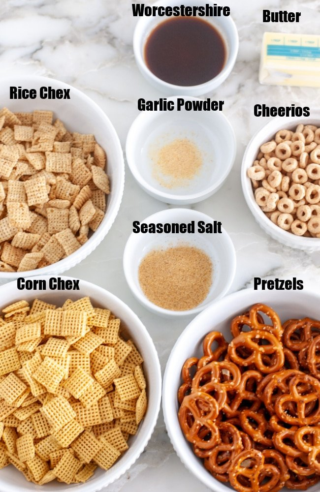 Chex cereal in a bowl, butter, pretzels in a bowl, Cheerios in a bowl.