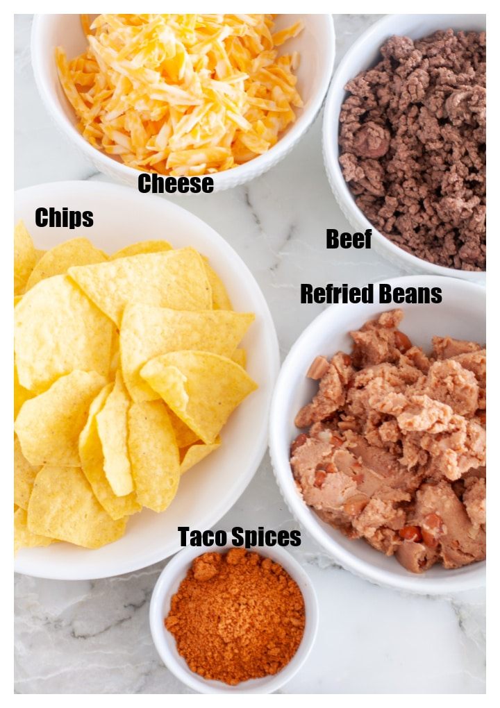 Bowl of chips, cheese, beans, beef and spices.