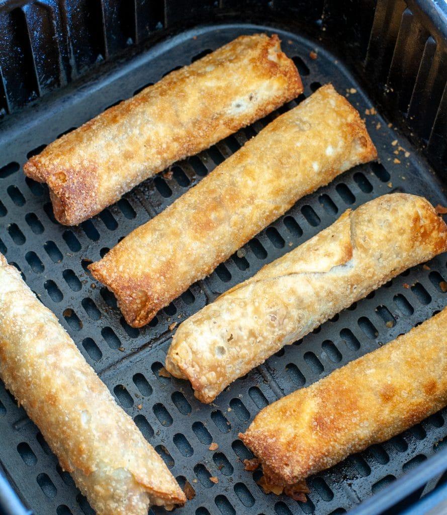 Egg rolls in an air fryer basket.