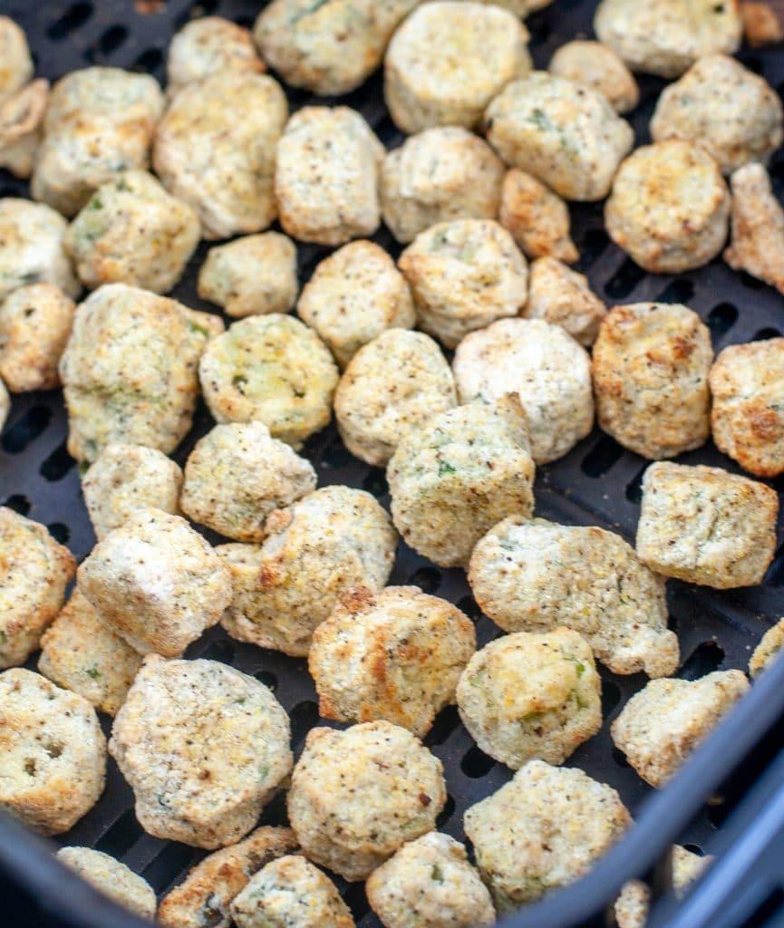 Cooked breaded okra in air fryer basket.