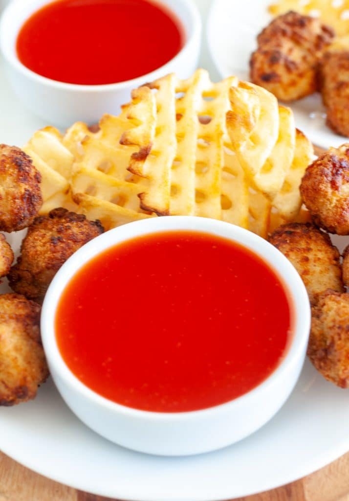 Bow of sweet and sour sauce surrounded by chicken nuggets.