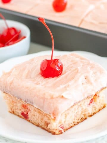Piece of cake on plate with cherry frosting and cherry on top.
