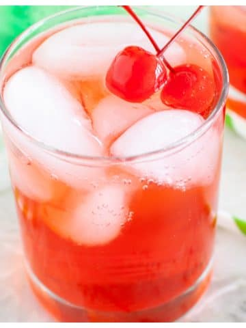 Glass of cherry soda and cherries.