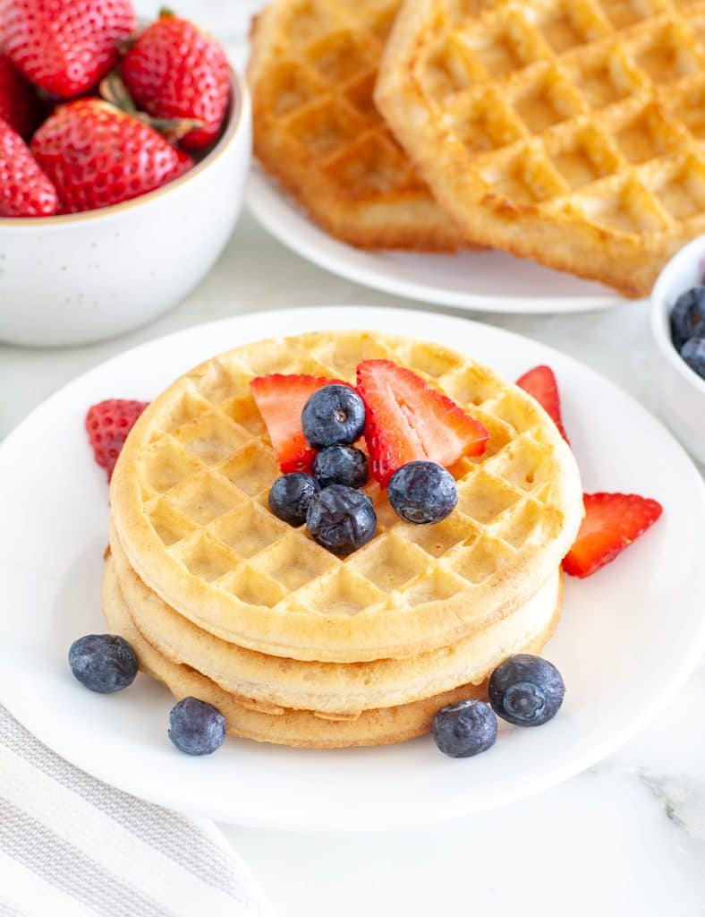 Waffles stacked on plate with berries.