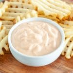 Bowl with mayonnaise sauce and waffle fries.