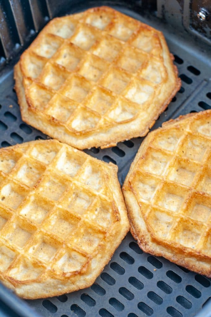 Cooked waffles in air fryer basket.