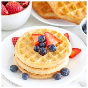Stack of waffles on a plate with berries.