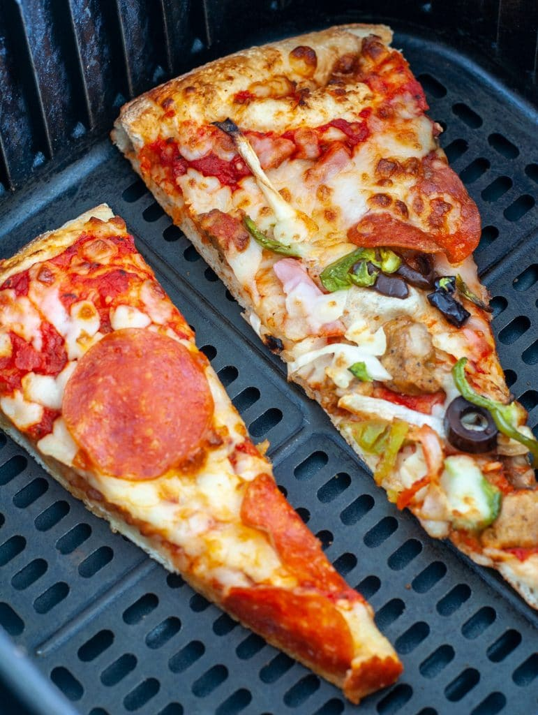 Pizza slices in air fryer basket.