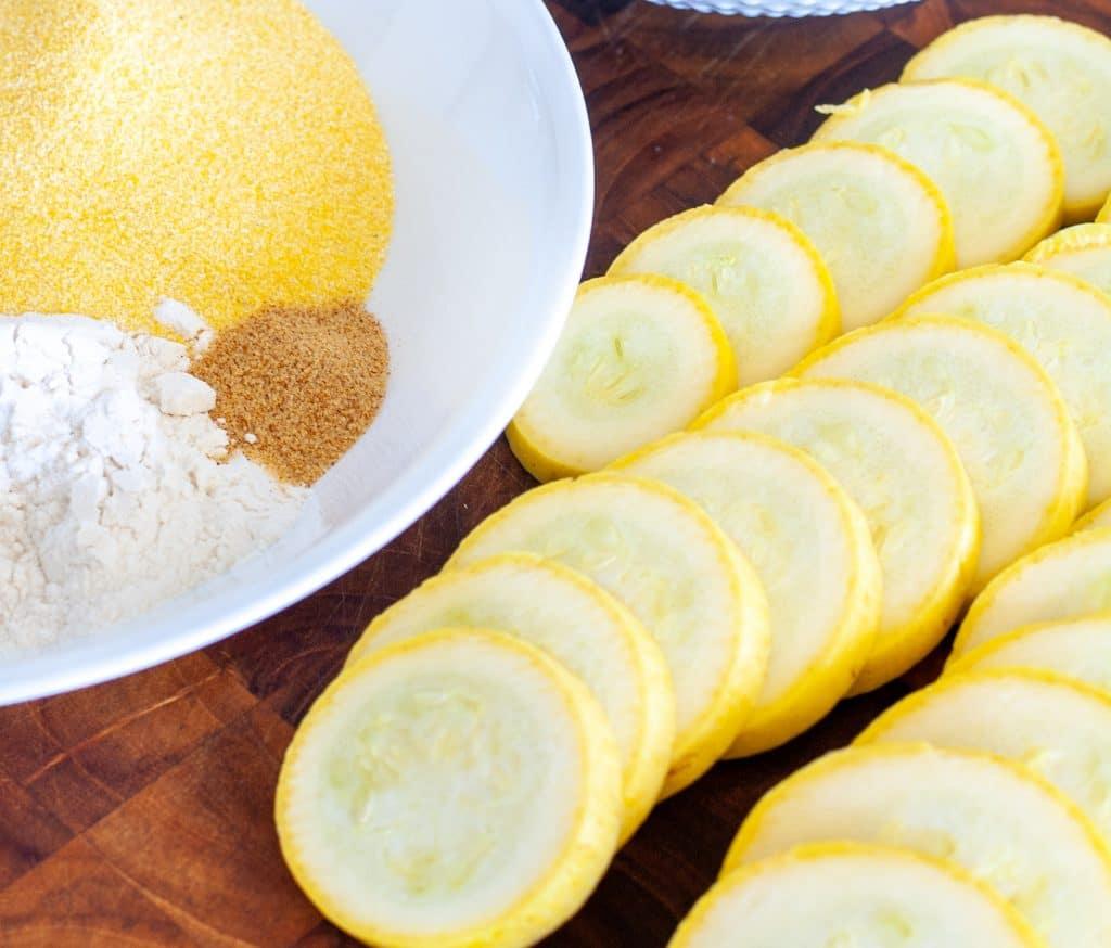 Sliced yellow squash on cutting board.