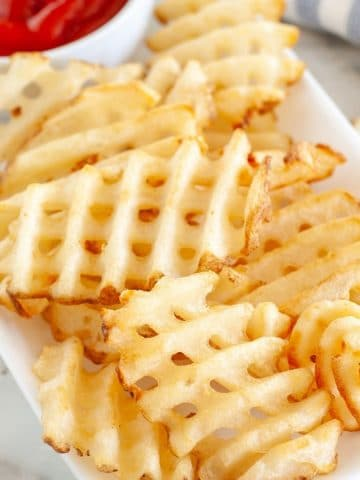 Waffle fries on a plate with bowl of ketchup.