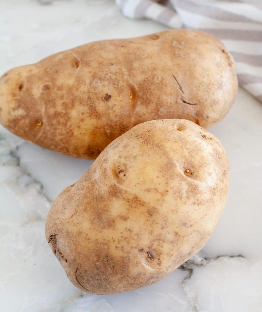Two russet potatoes on table.