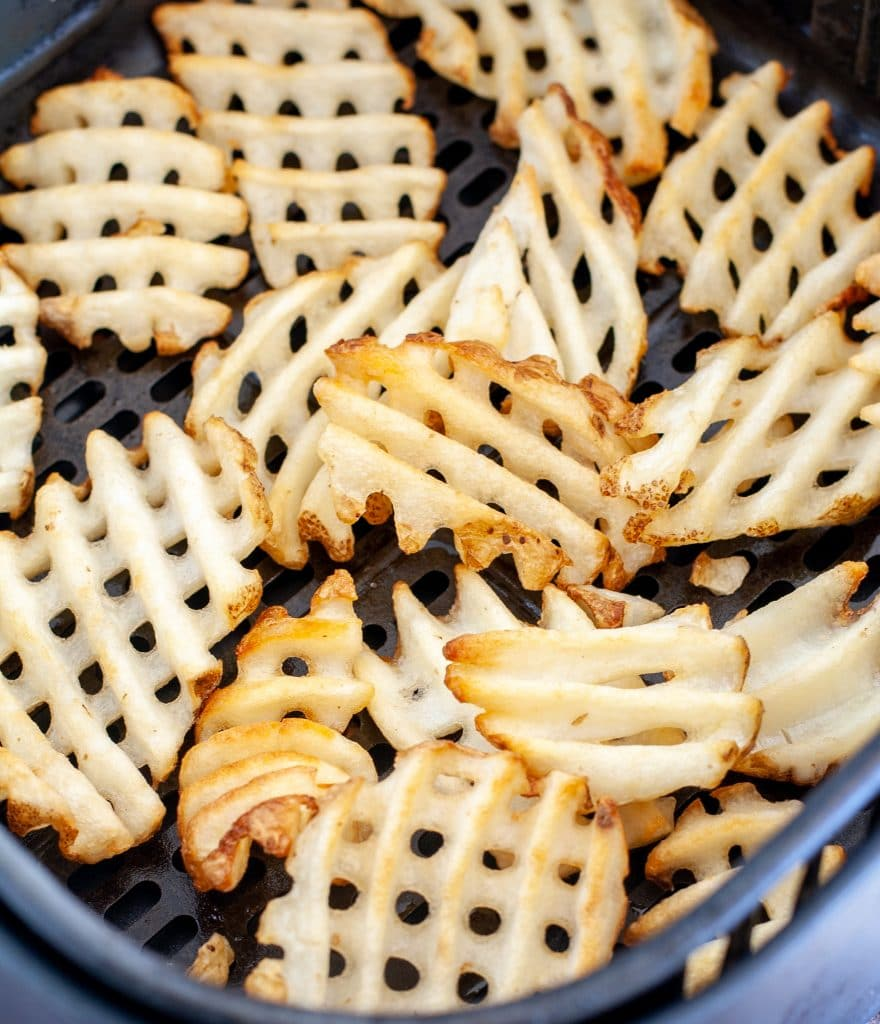 Cooked waffle fries in air fryer basket.