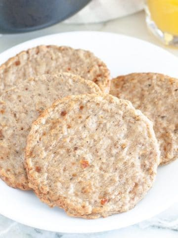 Plate with cooked breakfast sausage patties.