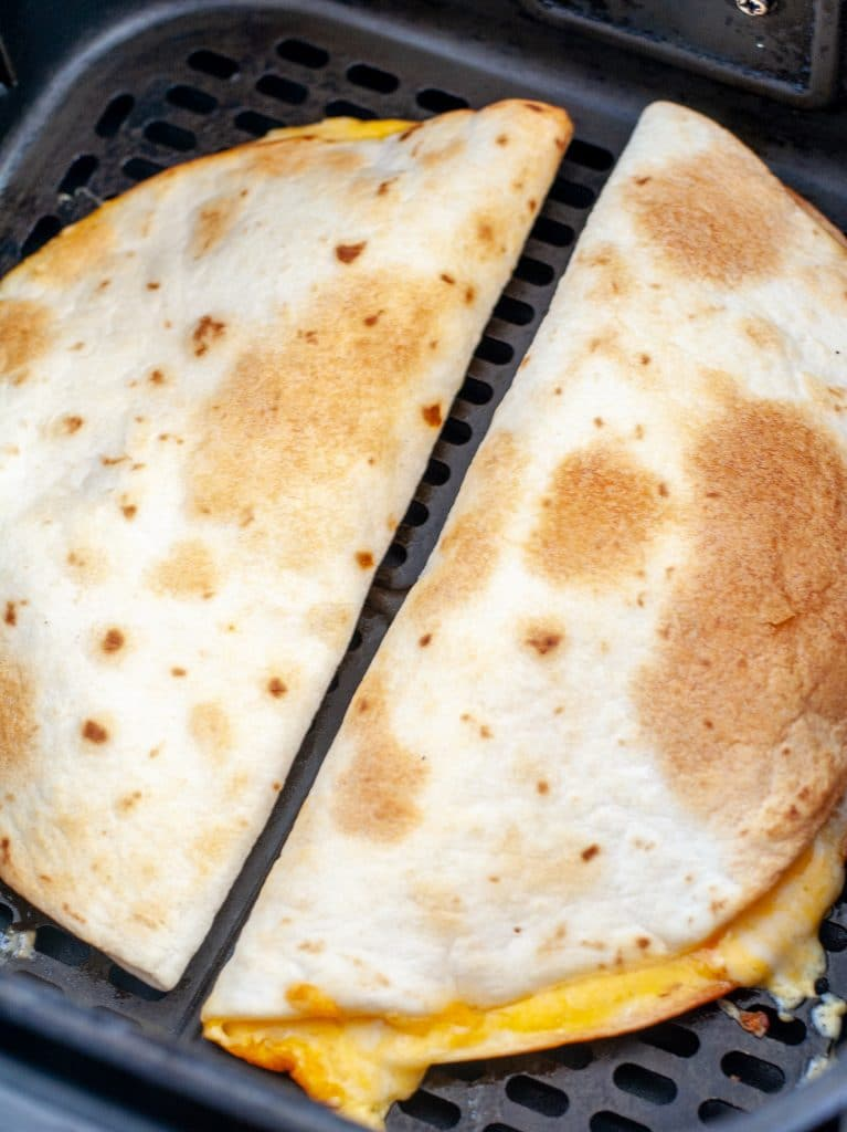 Cooked quesadilla in air fryer basket.