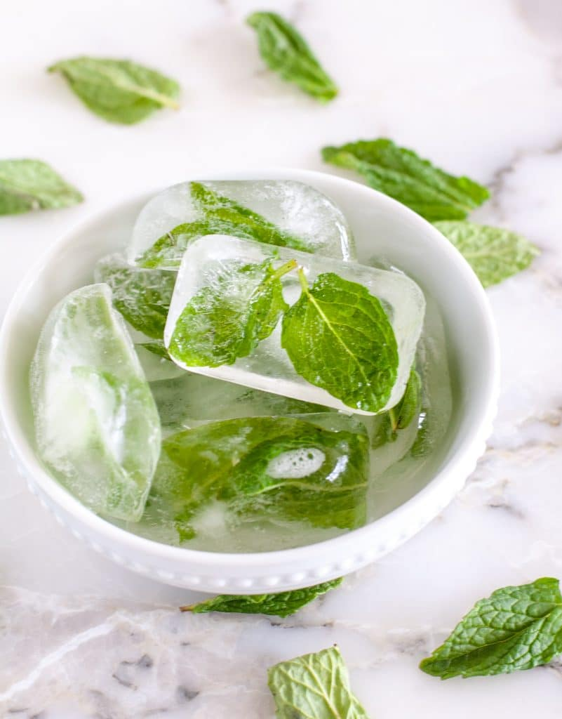 Mint leaves in ice cubes in a bowl.